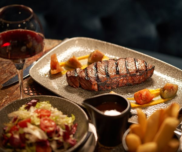 A Chargrilled Steak With A Glass of Red Wine At Crerar Hotels Restaurant