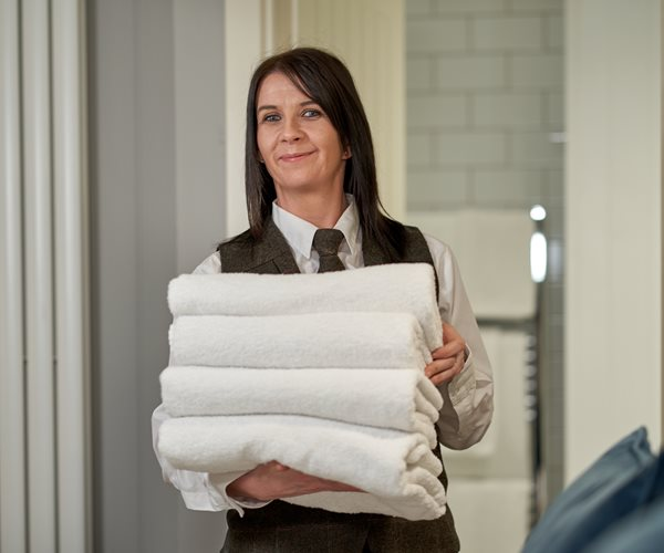 Housekeeper Delivering Fresh Room Towels At Crerar Hotels